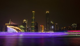 A long exposure picture of boats passing by a business area